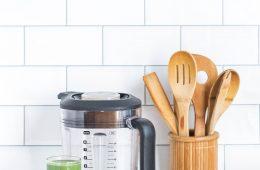 Mixer avec verre de boisson verte à côté et rangement vaisselle